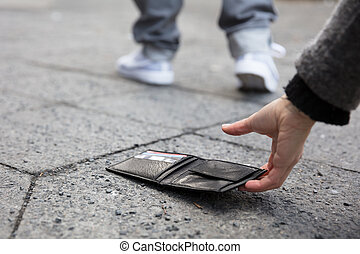 Person Picking Up A Lost Wallet
