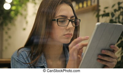 Close of beautiful young woman using tablet computer in cafe, view through the window