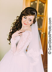 Close portrait of beautiful smiling bride woman with long curly hair posing in wedding dress at interior and smiling.