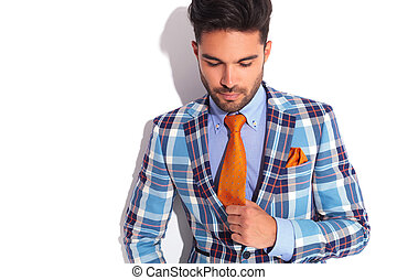 man in plaid jacket fixing his tie