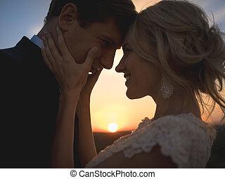 Close portrait silhouette in love wedding couple. Against the se