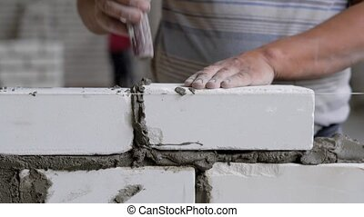 close shot at the builder hands, the man puts the bricks on...