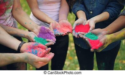 Close shot of people's hands holding colorful paint powder...