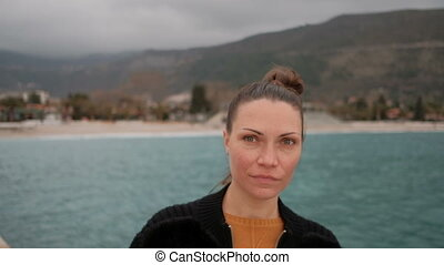 close shot of woman face on shore of lake, looking into...