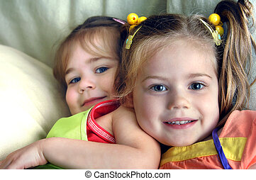 Close Siblings - Two young sisters tussle on the couch in ...
