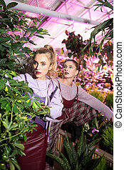 Nice attractive woman standing behind a plant
