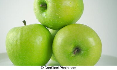 Close up 4K ProRes dolly shot of green apples and pouring water. White background