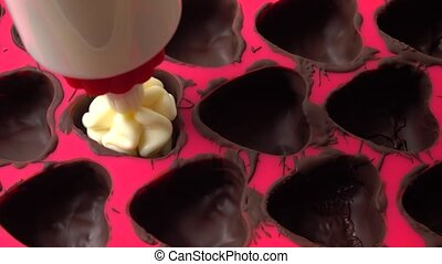 Close up 4K video of making heart shaped chocolates in red silicone form