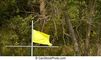 close-up. 4K. Yellow battered flag on the background of...