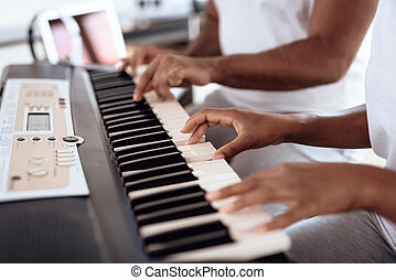 Close up. A black man sits in the living room of his apartment and plays a synthesizer. A girl is sitting next to him.