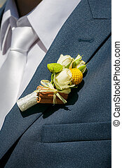 Close up a buttonhole of the groom from beige roses and cinnamon