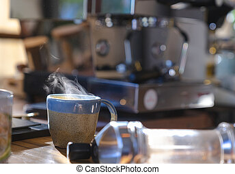 close up a ceramic cup of hot smoke coffee on wooden table with blurred coffee machine in background