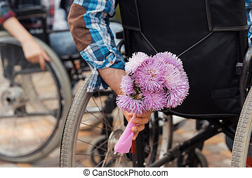 Close up. A couple of invalids on wheelchairs met in the park. A man is holding a bouquet of flowers.