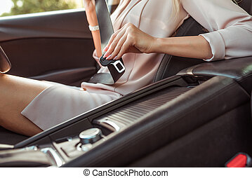 Close-up, a girl in a pink business suit, fastens her seat belt in the passenger compartment. Activation of airbags. In the summer in the city.