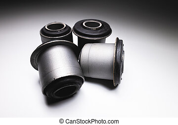 Close-up. A group of cylindrical silent blocks for the front suspension of an off-road vehicle. Contrast light low key