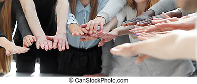 group of smiling young people joining their hands