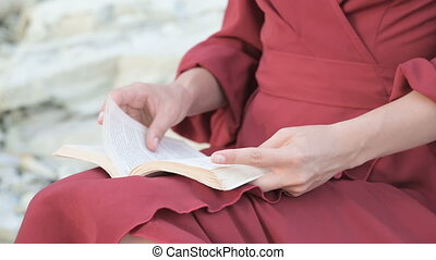 Close-up a hands attractive Caucasian girl in a red bright dress and a straw hat sits on a large stone by the sea at sunset and reads an interesting book