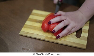 Close-up a hands of a young woman chopping vegetables on a wooden board.