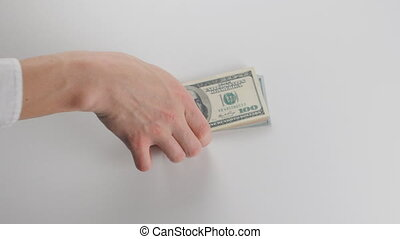 Close-up, a man gets a bundle of money. He considers dollar bills
