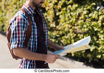 Close up. A man holds in his hands an expanded map of the world. He thinks where to go next.