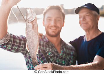 Close up. A man shows the old man a fish, which he just caught on his spinning