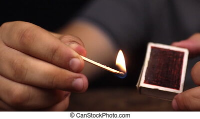 Close-up, a man takes a match out of the box and lights a ...