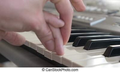 A child plays the piano  Close-up of baby girl's hands