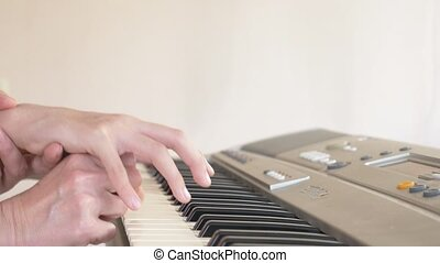 close-up. a piano teacher teaches a child to play the piano, setting the hands. 4k, slow motion