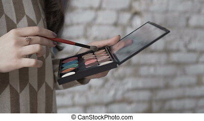 Close-up. A professional make-up artist picks up shadows on the brush. Make-up young woman artist's hand with brush and eye-shadow palette