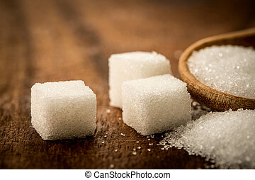 Close up a sugar cubes and cane in wooden spoon on the table ,retro color tone