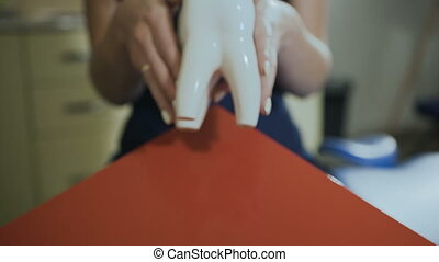 Close-up A tooth badge in the hands of a dentist. Stomatological services. Dental Implant