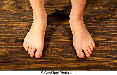 Close up a woman with itchy feet uses his big toe to scratch his other foot on wooden floor.