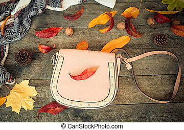 Close up a women is bag and autumn leaves on a wooden background . Top view
