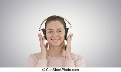 A young woman listening to music in headphones on gradient background.