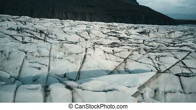 Close-up aerial view of the Vatnajokull glacier with black ash. Drone flying over the big iceberg in Iceland.