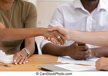 Close up African American businesswoman shaking hand of business partner at meeting, greeting, making partnership agreement, signing contract, hr manager hiring new employee, successful negotiations