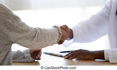 Close up african american doctor shaking hands with young woman.