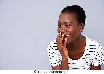 Close up african american woman smiling with her hand covering mouth on gray background