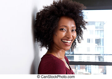 Close up african woman with curly hair leaning to wall at home and smiling
