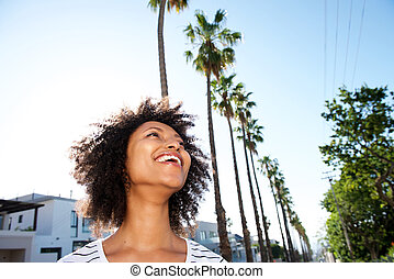 Close up african young woman outdoors and smiling