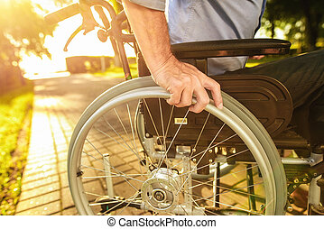 Close up. An old man is sitting on a wheelchair in the park
