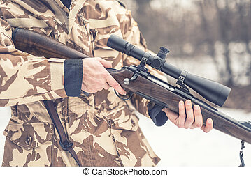 Close up and details of a man wearing a camouflage suit holding a sniper, rifle or gun