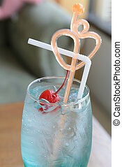 close up and soft focus of blue ocean, curacao with red maraschino cherry on top, heart shape stirring, focused on the red cherry and shot at ambient light in a cafe