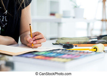 Close-up angle view of a female painter drawing draft at ...