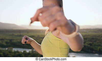 Close up. Angry kick boxing girl perform training on the top of mountain on sunset or sunrise at summer. Young woman doing boxing and looking on the camera. Beautiful female boxer training on the ourdoors in the morning