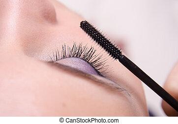 Close-up applying mascara on eyelashes - Makeup artist...