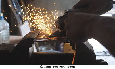 Close up arms of male welder sawing metal with a circular...