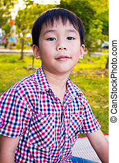 Close up asian boy relaxing in the park. Young kid outdoors