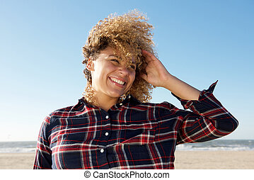 Close up attractive african american woman smiling with hand in hair at the beach