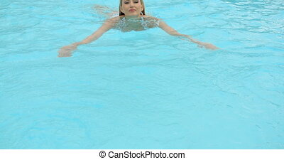 Blond Woman Leaning Against The Edge of the Pool